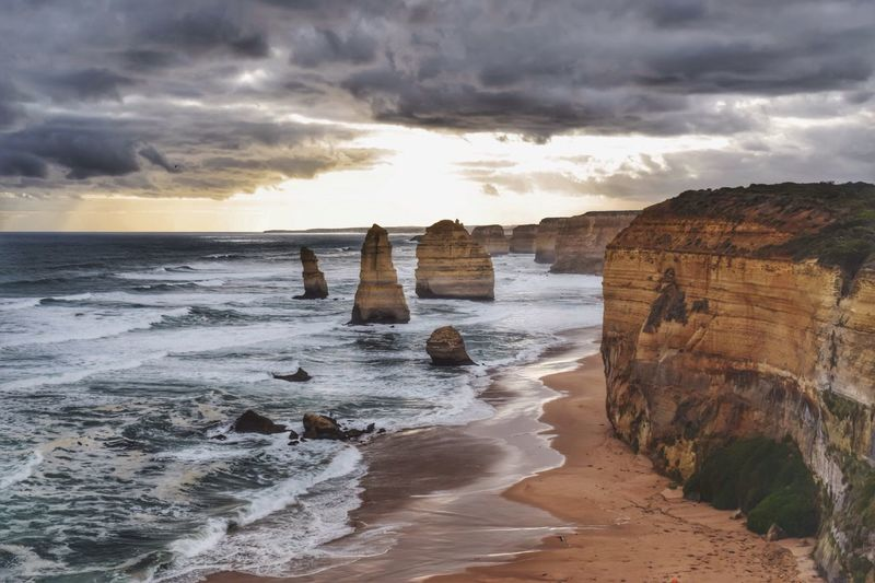 Scenic view of twelve apostles sea rocks and sea against cloudy sky
