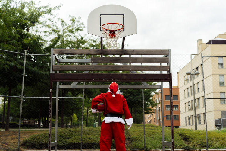 Rear view of man standing by basketball hoop