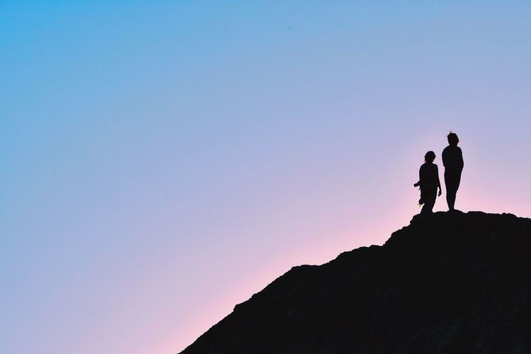 LOW ANGLE VIEW OF SILHOUETTE PEOPLE STANDING ON ROCK AGAINST CLEAR SKY