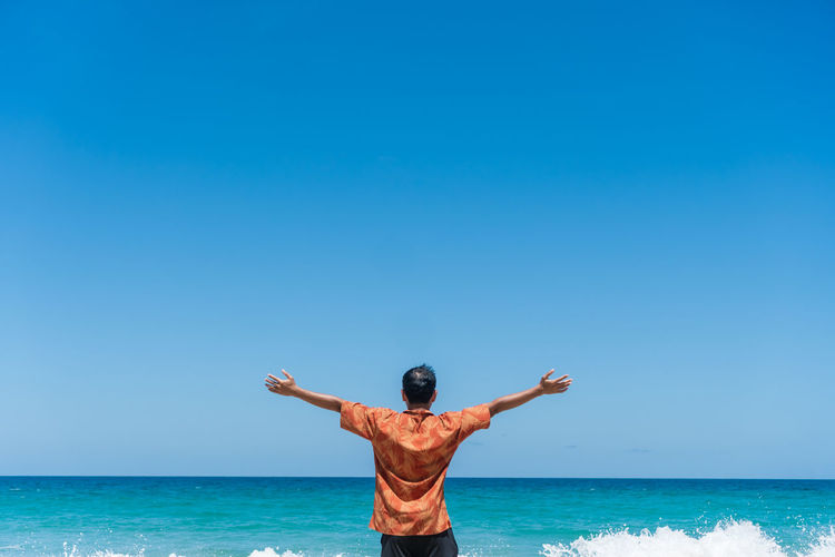 Rear view of man with arms outstretched standing at beach against sky