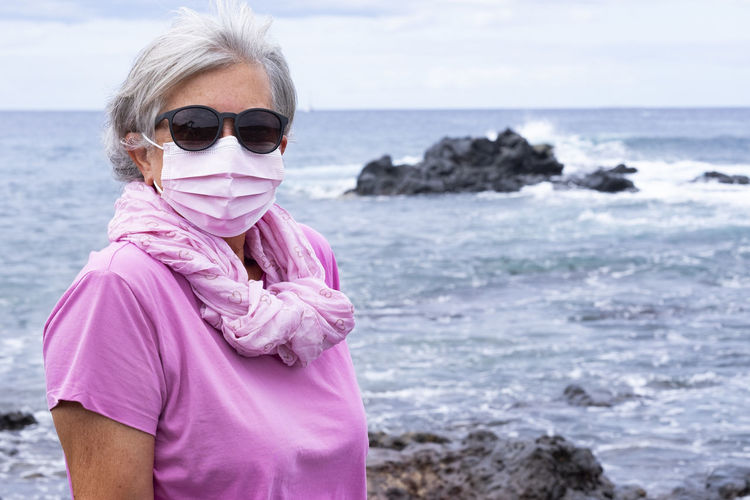 Portrait of senior woman wearing mask standing against sea