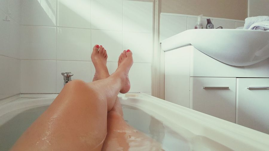 Low section of sensuous woman relaxing in bathtub at bathroom