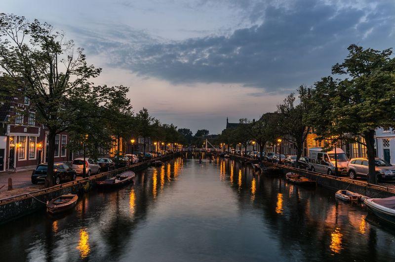 Canal Amidst Illuminated Trees Against Sky