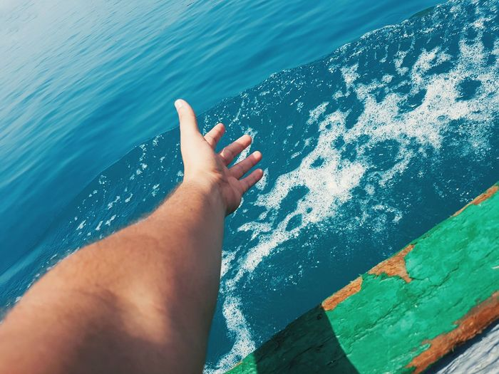 Cropped hand of man gesturing while traveling on boat in sea