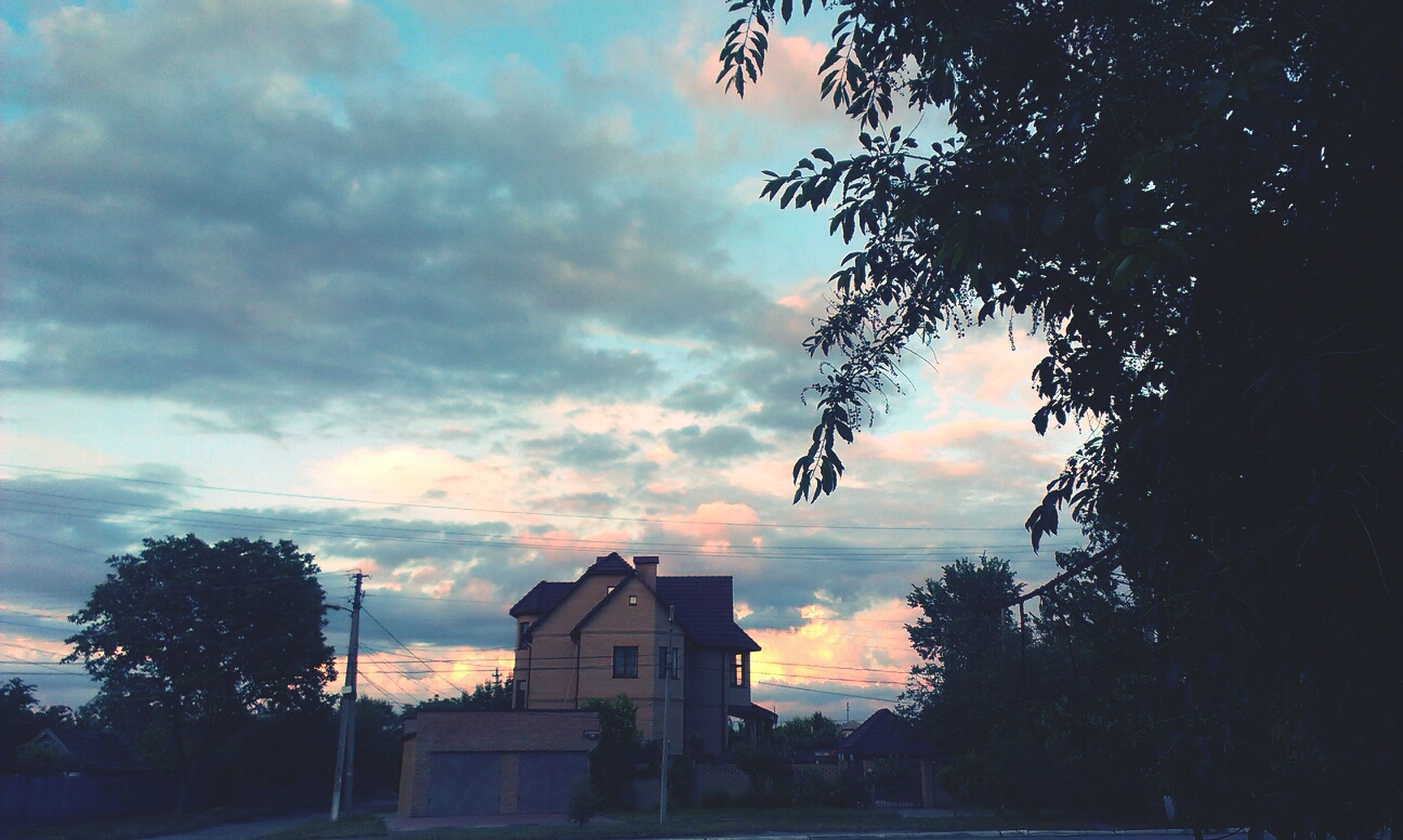 sky, cloud - sky, tree, building exterior, silhouette, built structure, architecture, cloudy, low angle view, sunset, cloud, dusk, house, weather, nature, bare tree, dramatic sky, outdoors, overcast, street light