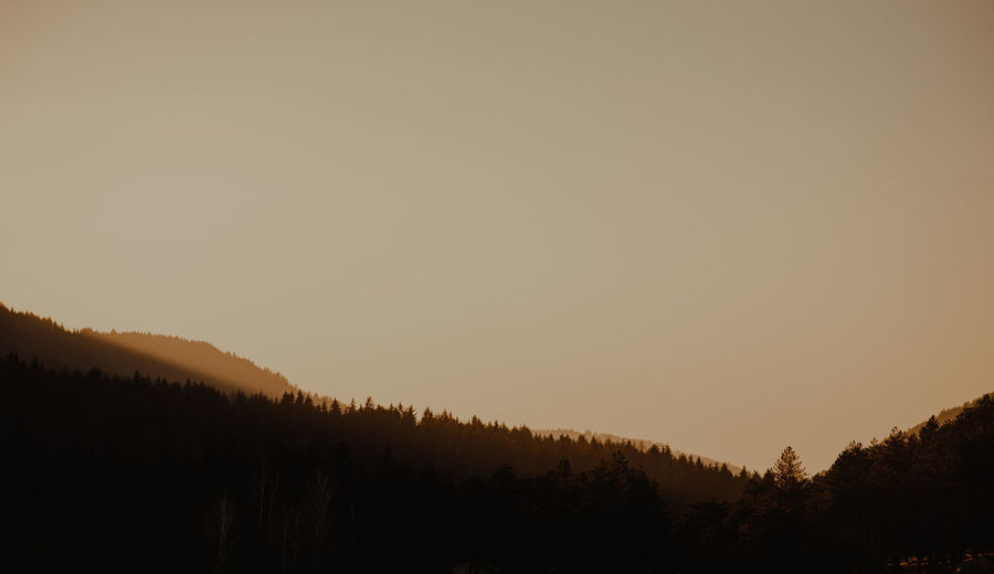 Scenic view of silhouette mountain against sky at sunset
