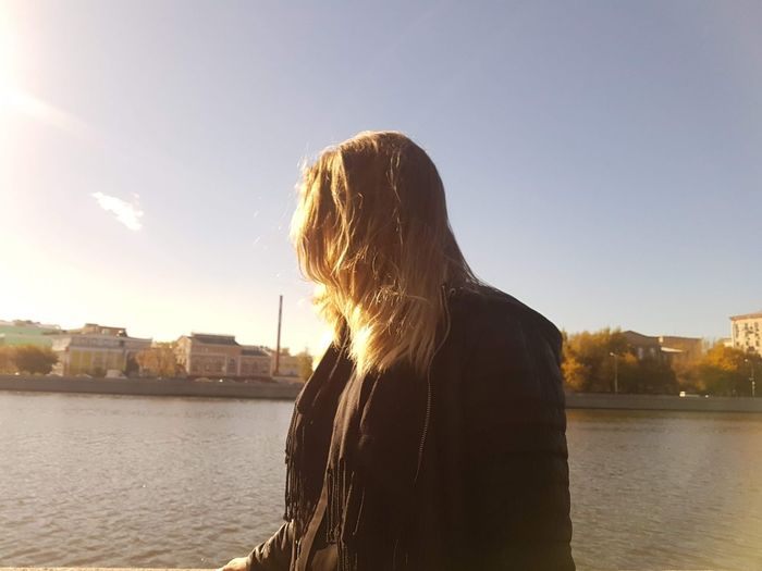 Rear view of woman against river in city