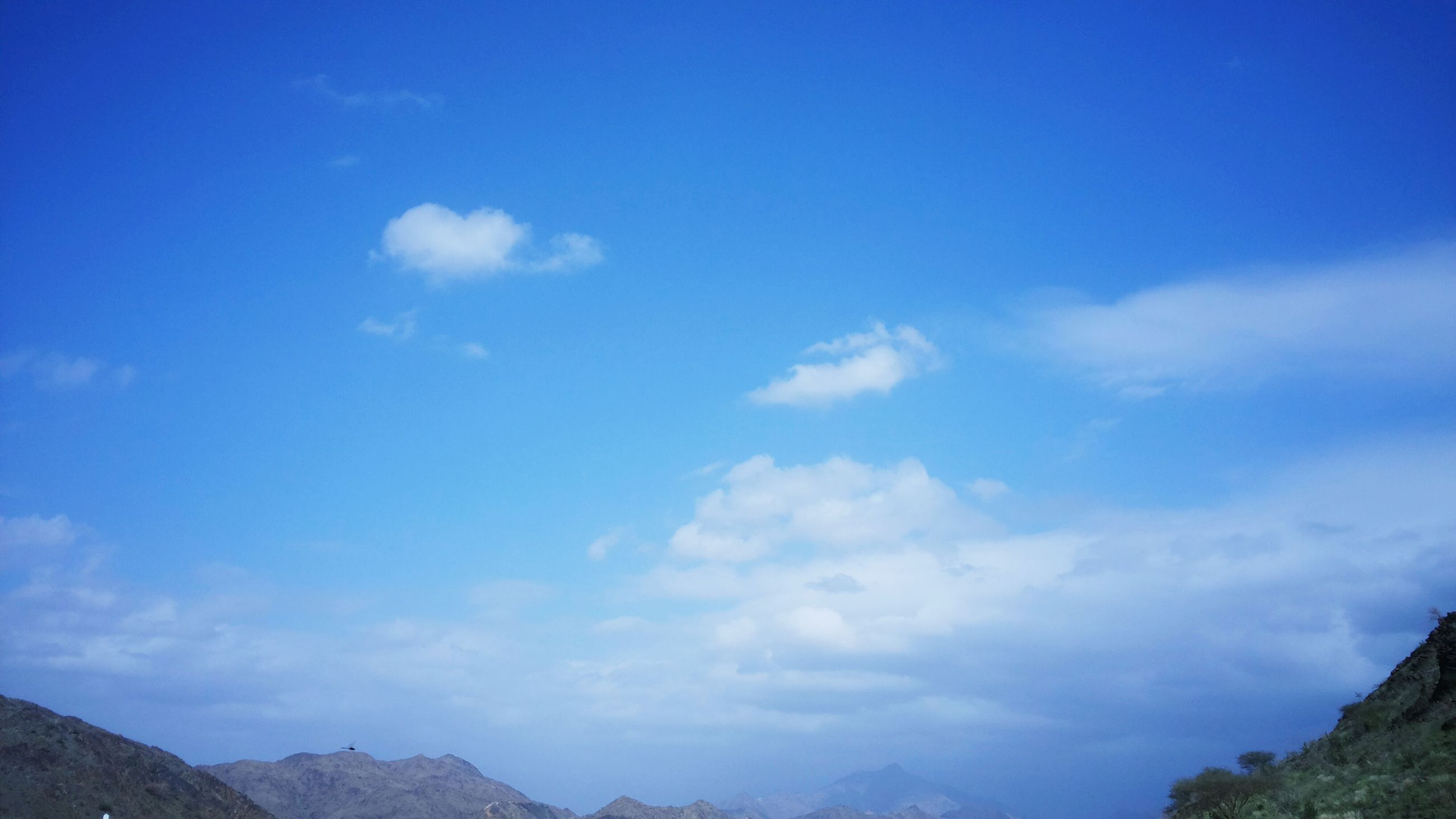 blue, mountain, sky, tranquility, tranquil scene, scenics, beauty in nature, nature, low angle view, mountain range, cloud - sky, landscape, cloud, idyllic, non-urban scene, day, outdoors, copy space, no people, remote
