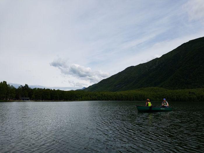 People fishing in mirror lake against sky