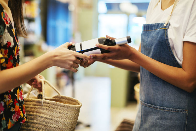 Midsection of woman using mobile phone at store