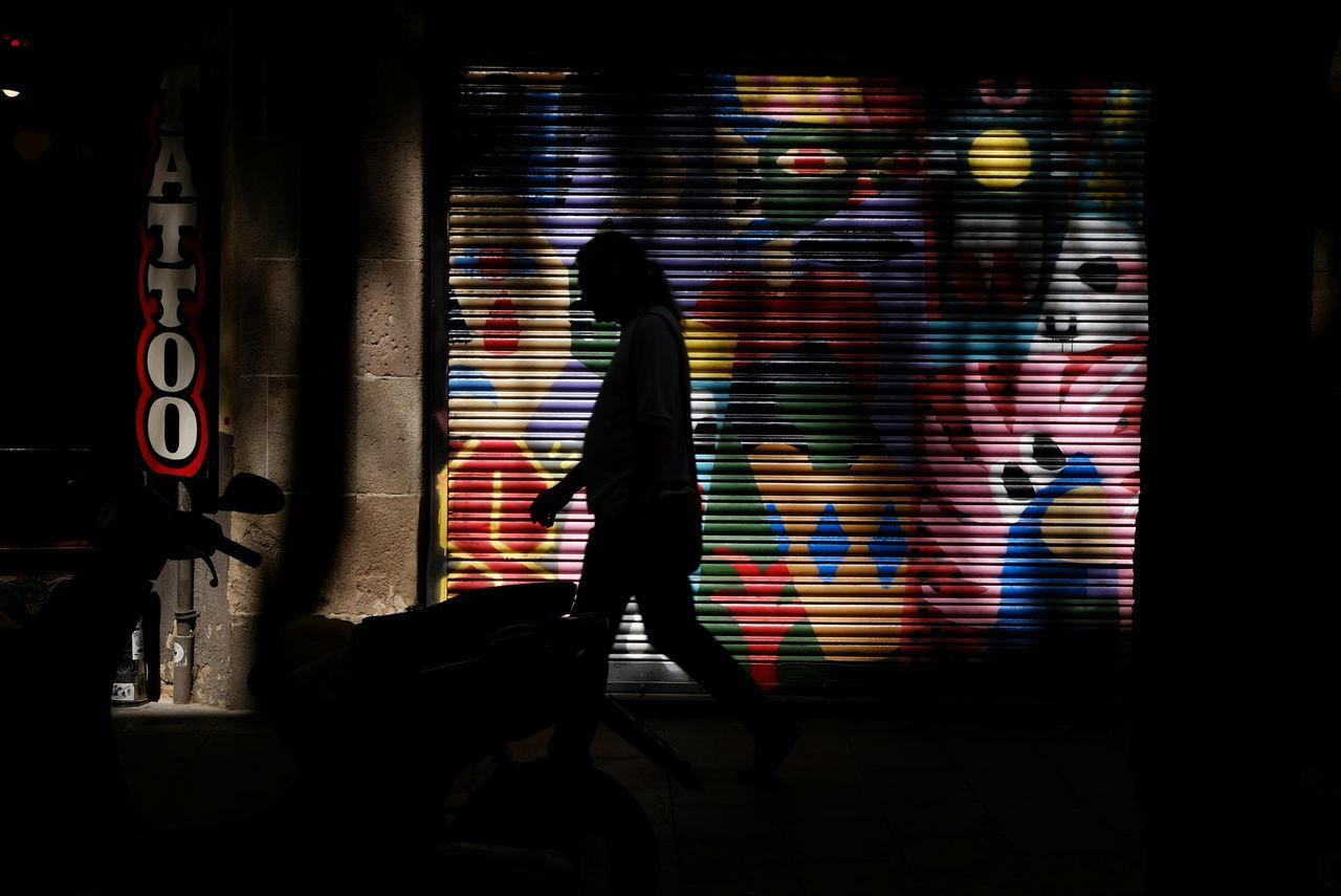 SILHOUETTE MAN WALKING AGAINST ILLUMINATED WALL IN CITY