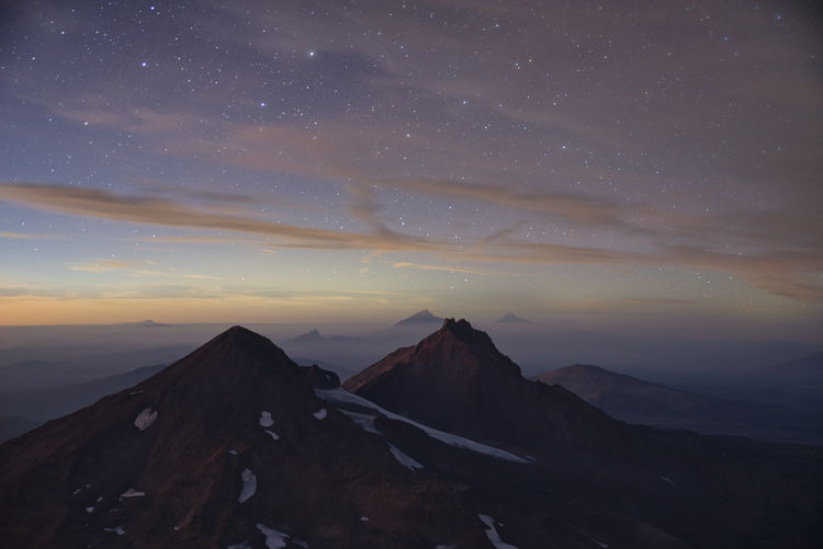 Night shot of stars with volcanoes in the background right after sunset