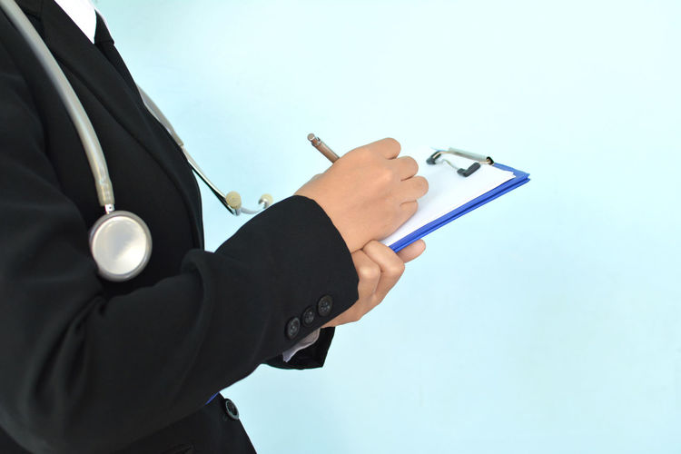 Close-Up Of Man With Stethoscope Writing