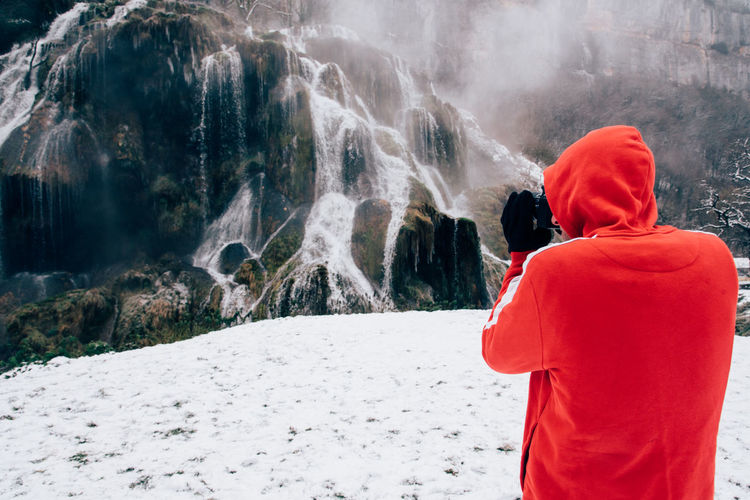 Man photographing waterfall during winter