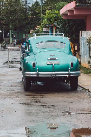 Vintage car on street by buildings