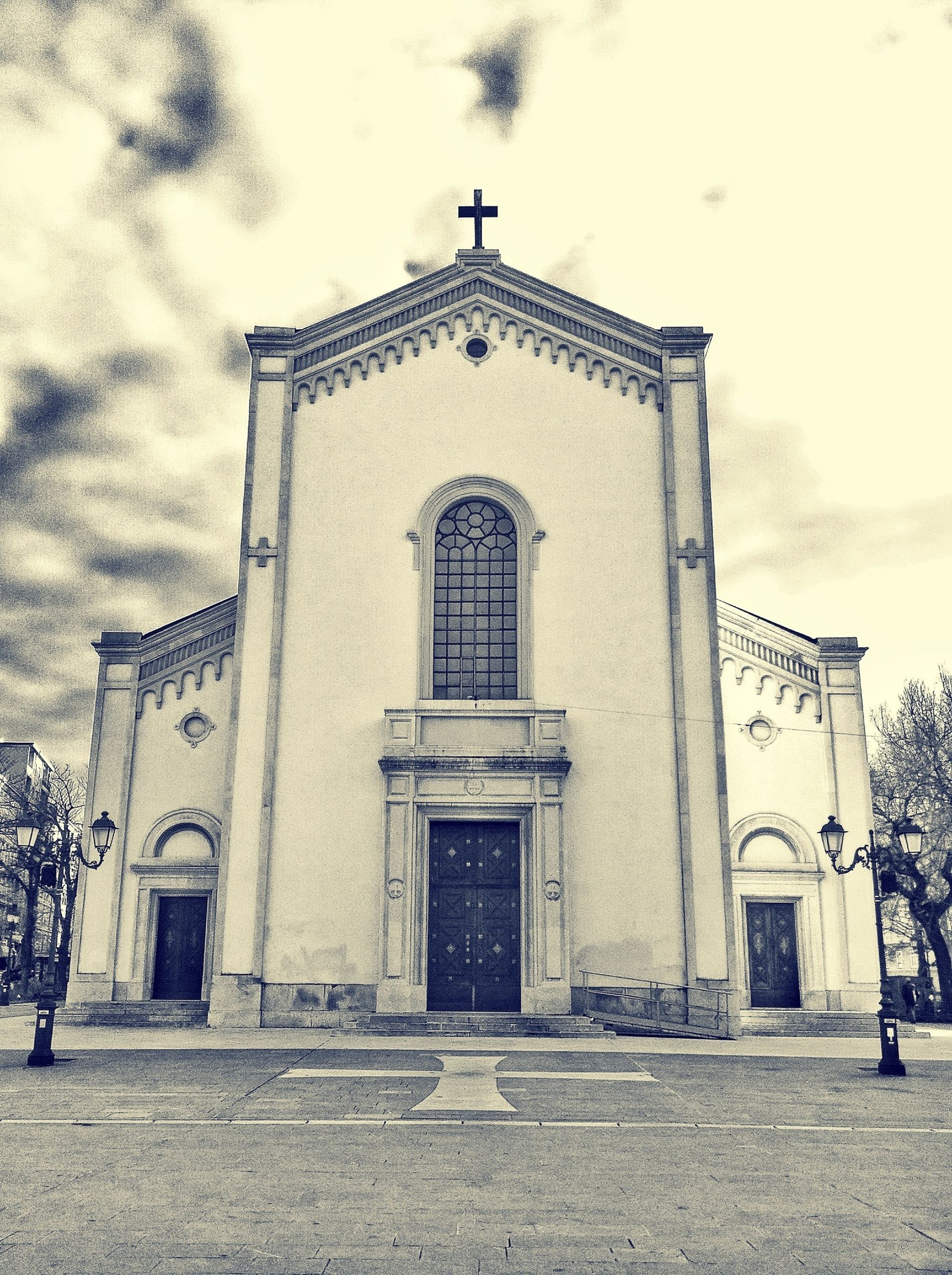 building exterior, architecture, built structure, church, religion, place of worship, sky, spirituality, facade, entrance, door, low angle view, cross, cloud - sky, outdoors, day, arch, window
