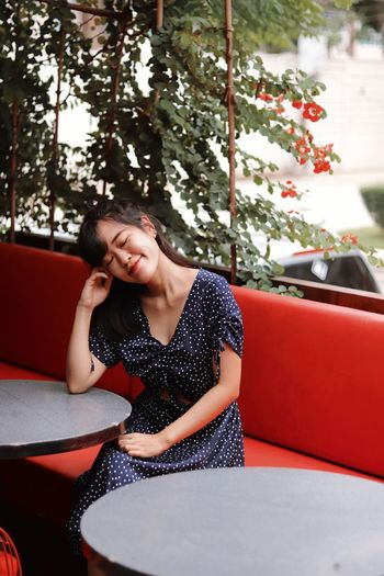 Beautiful woman sitting on table against trees