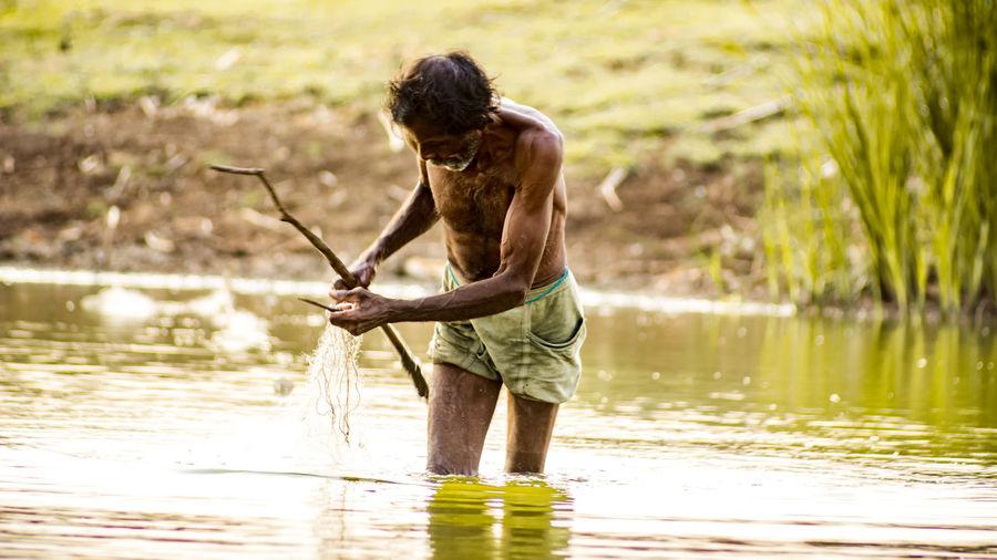 Shirtless man holding stick while standing in lake