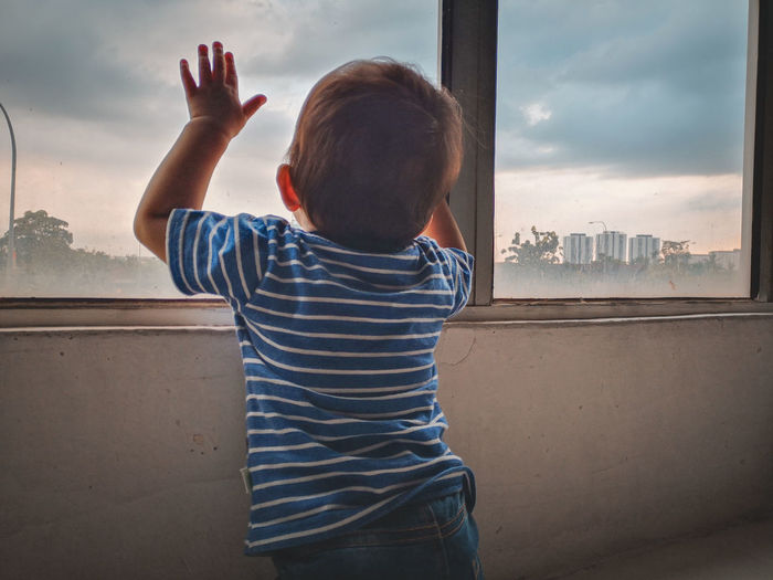 Rear view of boy with arms raised by window