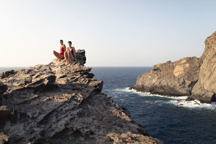 PEOPLE SITTING ON ROCK IN SEA AGAINST CLEAR SKY
