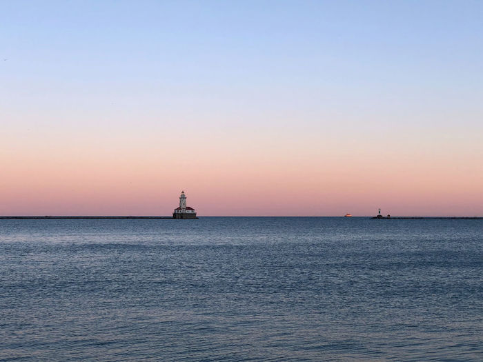 Silhouette lighthouse in sea against clear sky during sunset