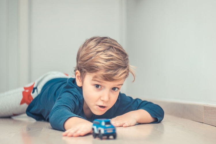Portrait of boy lying on table at home