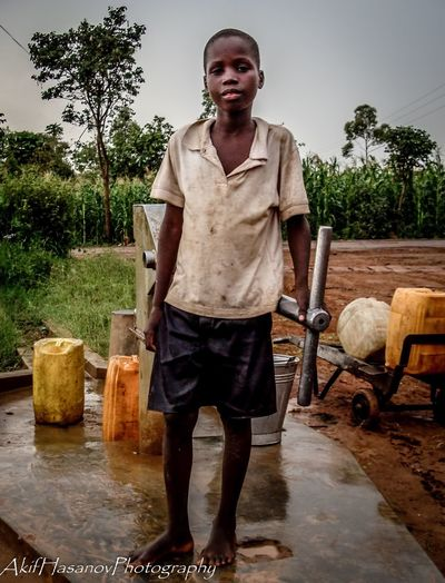 My neighbor. Real People One Person Portrait Standing Young Adult Day Water_collection Waterpump Street Photography