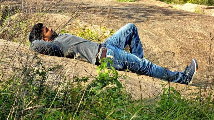 Side View Full Length Of Man Relaxing On Rock
