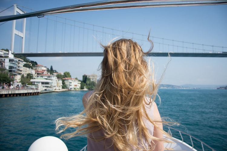 Adult Architecture Blond Hair Bridge - Man Made Structure Building Exterior Built Structure City Clear Sky Day Long Hair Nature Nautical Vessel One Person Outdoors Real People Rear View Sailing Sea Sky Transportation Water Women Yacht Young Adult Young Women