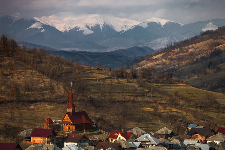 Incredible landscapes from Romania. Church Cloudy Hills Houses Maramures Romania Rural Building Exterior Built Structure Landscape Mountain Mountain Range Nature No People Outdoors Religion Sky Snow Spring Springtime Village