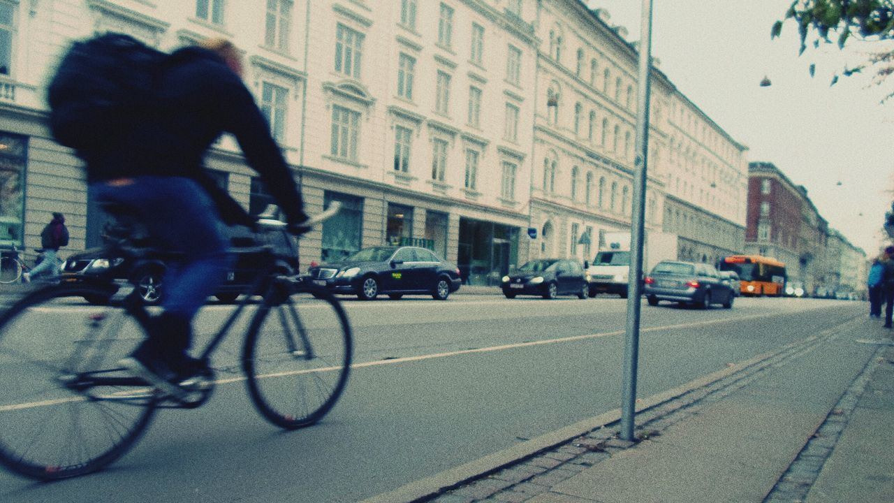 bicycle, transportation, street, real people, city, land vehicle, mode of transport, men, one person, outdoors, road, cycling, motion, city life, riding, day, architecture, full length, building exterior, one man only, sky, adult, people, adults only