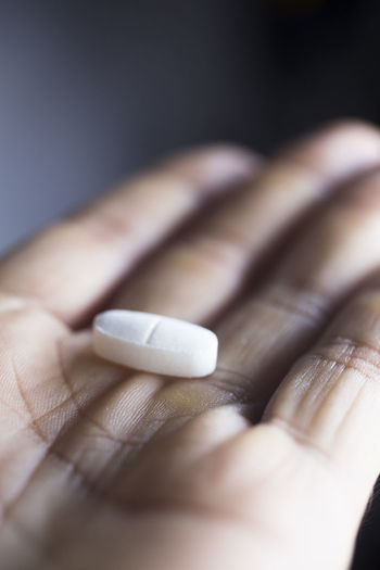 Cropped hand holding pill