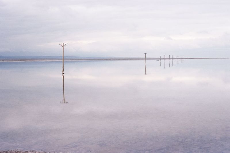 Reflection of wooden post in lake against sky