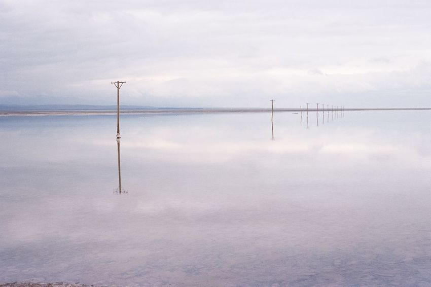 Film Photography Water Tranquility Nature Scenics Tranquil Scene Cloud - Sky Beauty In Nature Sky Outdoors Reflection Lake No People Day Wooden Post Wind Power Wind Turbine Industrial Windmill Windmill