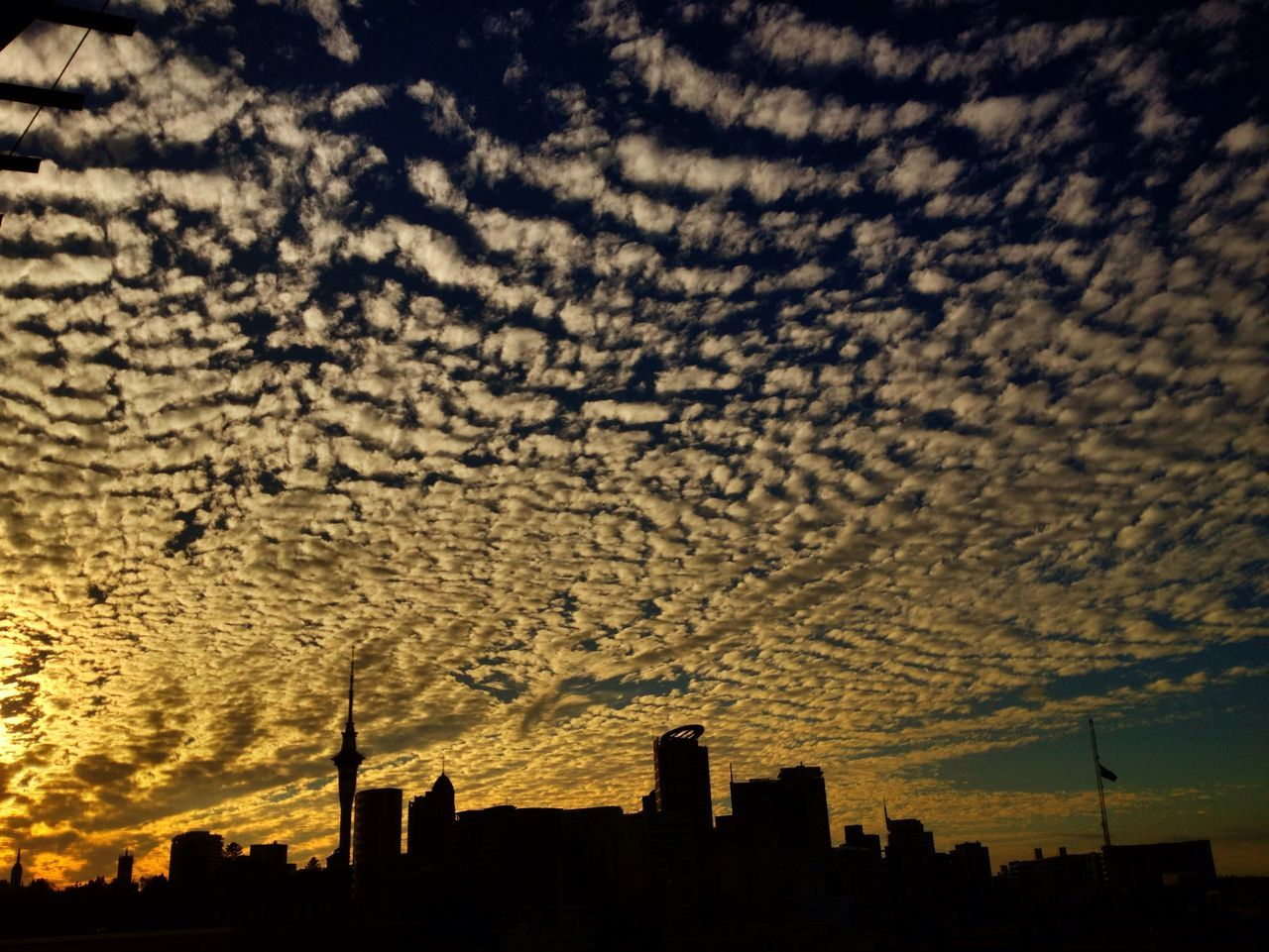 Low angle view of silhouette cityscape against cloudy sky during sunset
