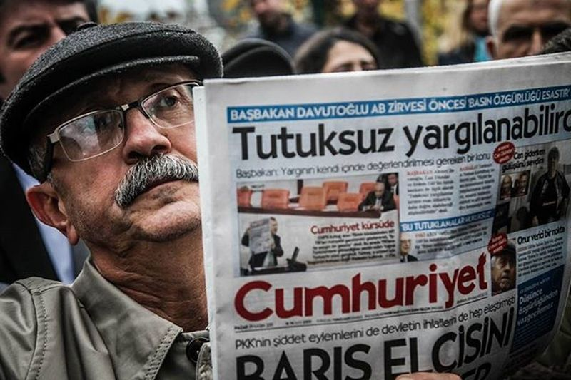 A member of a journalism union holds copy of Cumhuriyet daily newspaper on November 29,2015 in Istanbul during a demonstration after the arrest of their Editor in Chief.A court in Istanbul charged two journalists from the opposition Cumhuriyet newspaper with spying after they alleged Turkey's secret services had sent arms to Islamist rebels in Syria,Turkish media reported.Editor-in-chief Can Dundar and Erdem Gul,the paper's Ankara bureau chief are accused of spying and 'divulging state secrets'.Both men were placed in pre-trial detention. Candundar ErdemGül Cumhuriyet