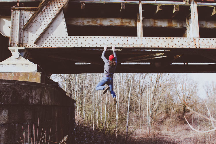 Rear view of young man with long hair climbing abandoned railway bridge