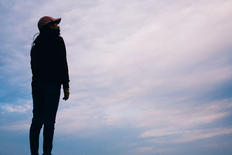 Low angle view of silhouette woman standing against sky during sunset