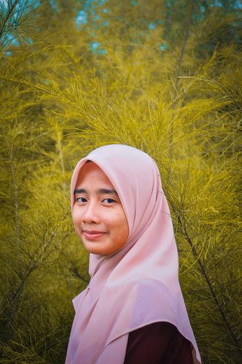 Portrait of woman in hijab by plants