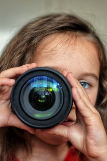 Close-up portrait of girl holding camera