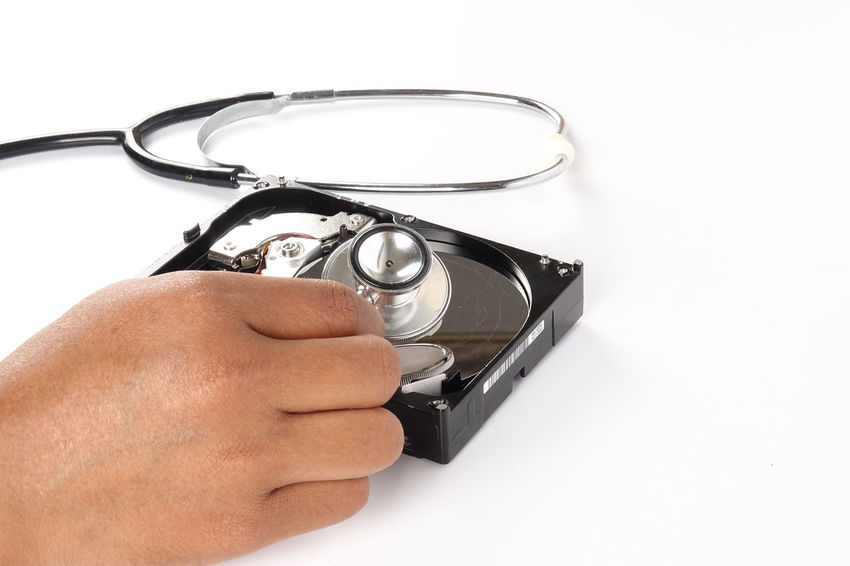 RECOVERY AND REPAIR TECHNOLOGY CONCEPT: Hard Disk Drive (HDD) with stethoscope isolated on white. Indoors  Technology Recovery Data Hard Disk Drive Media Hard Disk Stethoscope  Laptop Computer Repair Security Conceptual Conceptual Photography  Media Storage