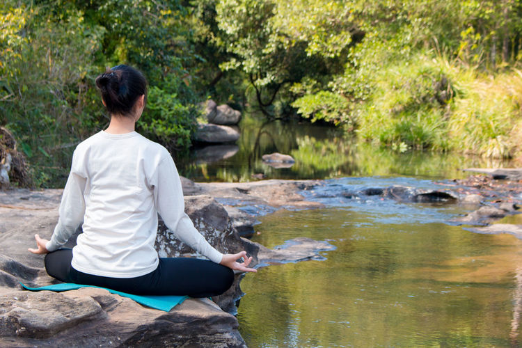 Rear view of young woman practicing yoga on rock by stream in forest