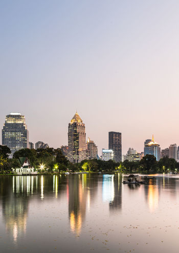 Reflection of office buildings in the water of a pond in Lumphini park in the heart of Bangkok, Thailand capital city in Southeast Asia Architecture ASIA Bangkok Building Exterior Built Structure Buisness City Cityscape Illuminated Modern No People Outdoors Pond Public Park Reflection Sky Skyscraper Sunset Thailand Travel Destinations Urban Skyline Water Waterfront