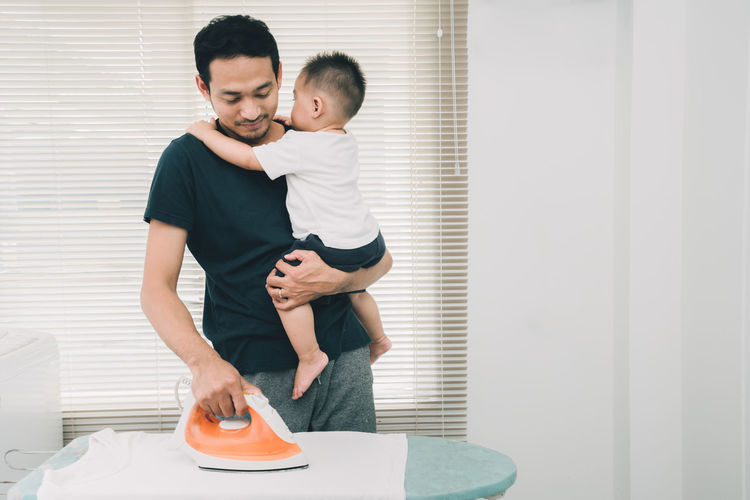 Happy family concept, Father pick up little son his ironing clothes on ironing board doing chores at home in holidays weekend. Males  Child Men Family Childhood Boys Emotion Parent Togetherness Indoors  Love Adult Family With One Child Son Lifestyles Women Standing Positive Emotion Care Innocence