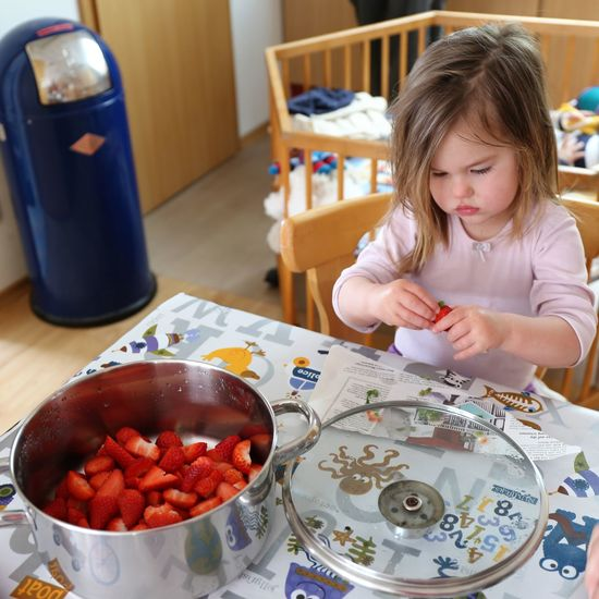 High angle view of cute girl cleaning strawberry on table at home