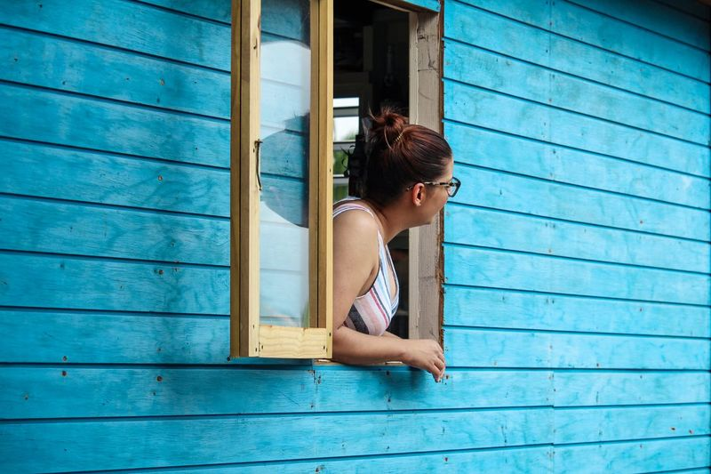 Looking Through Window Window Blue One Person Sitting Women Curly Hair Architecture Lifestyles Emotion Hairstyle Outdoors Real People Wood - Material