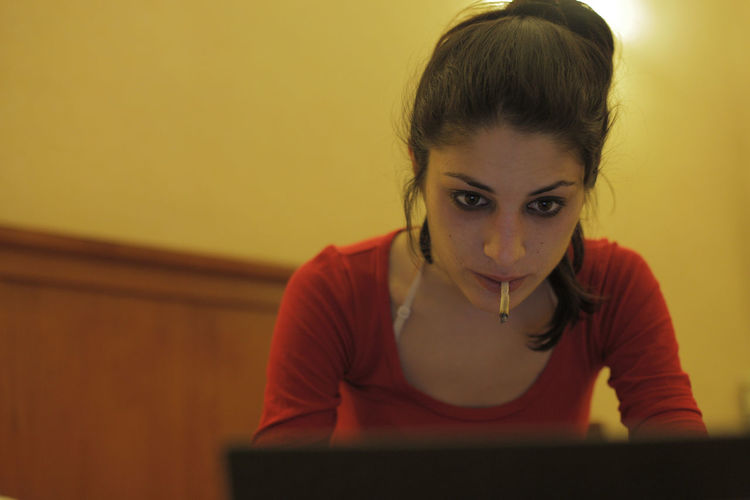 Woman Smoking Cigarette While Using Laptop At Home