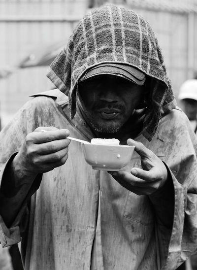Senior man eating porridge while standing on street