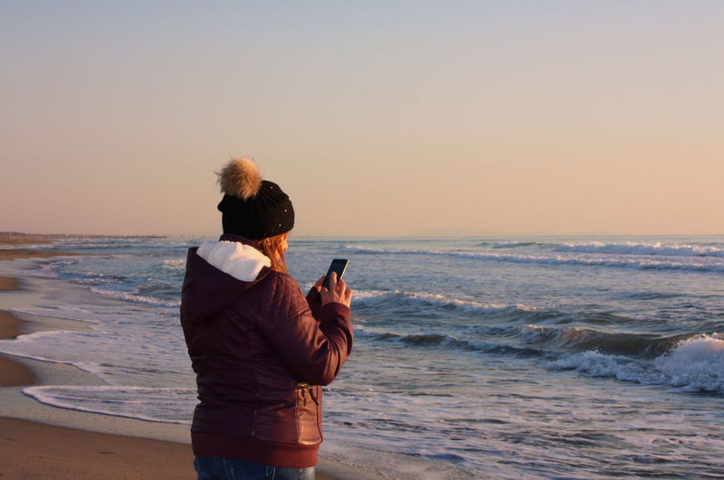 Rear view of woman photographing at beach during sunset