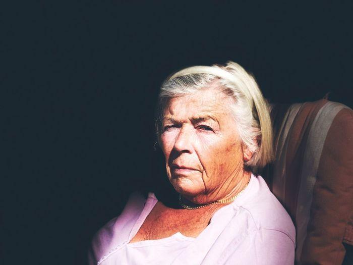Portrait of senior woman against black background